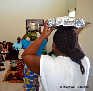 The women bring in the cooked food to the room where the in-laws sit. Each dis is brought in a pot and laid on the floor before the guests.
